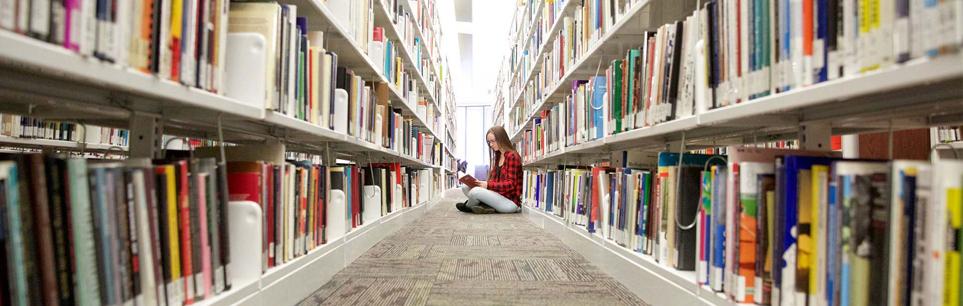 Student reading between Library shelves